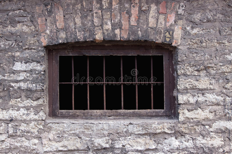Old rusty prison window. Brick wall stock photography
