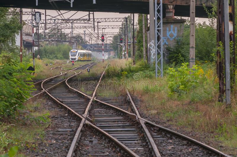 Old rusty rail trucks junction with train in background. With bushes on the side stock photos