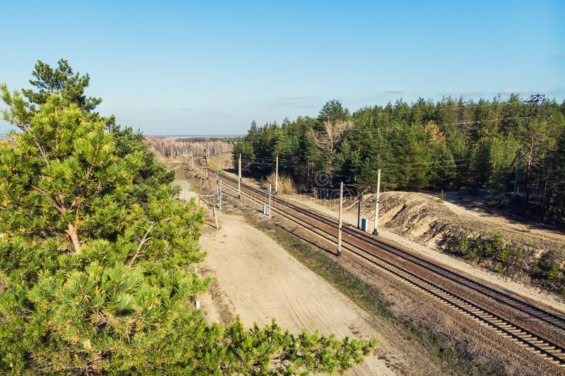 Old rusty railriad track curve among evergreen coniferous pine forest and blue sky on background. Railroad, landscape, tree, train, nature, transportation royalty free stock photography