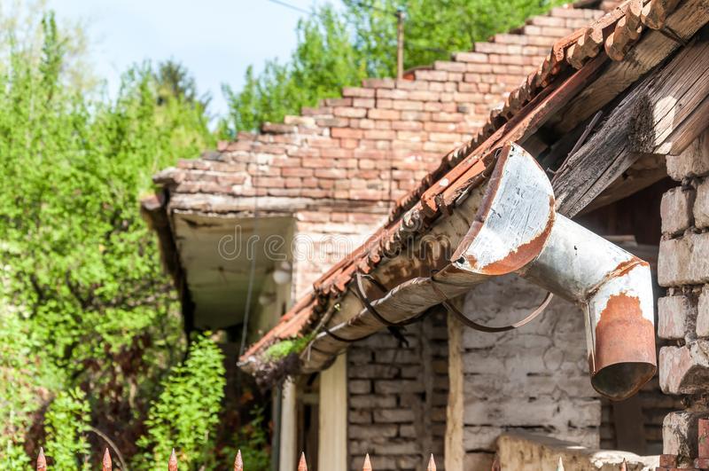 Old and rusty rain gutter on abandoned house damaged by age and water close up.  royalty free stock image