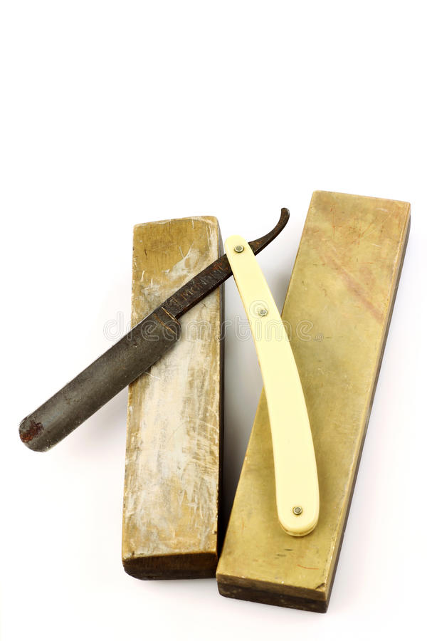 Old rusty razor and two sharpening stones. On a white background stock photo