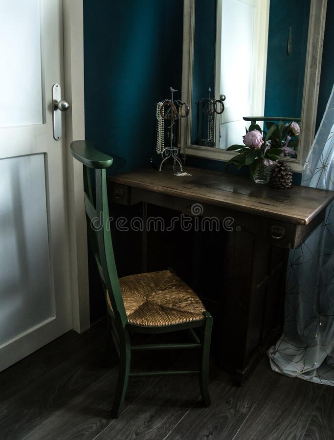 Retro interior design with old jewelry, peony flower and sewing table. Old, rusty retro style room with petrol blue walls, big mirror and peony flower as a royalty free stock photos