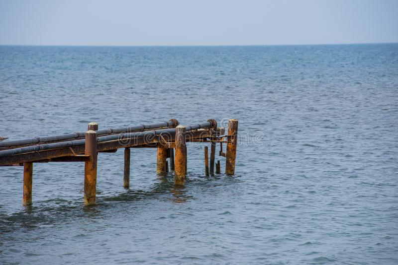 Old rusty sea berth for boats with pipes. In summer royalty free stock image