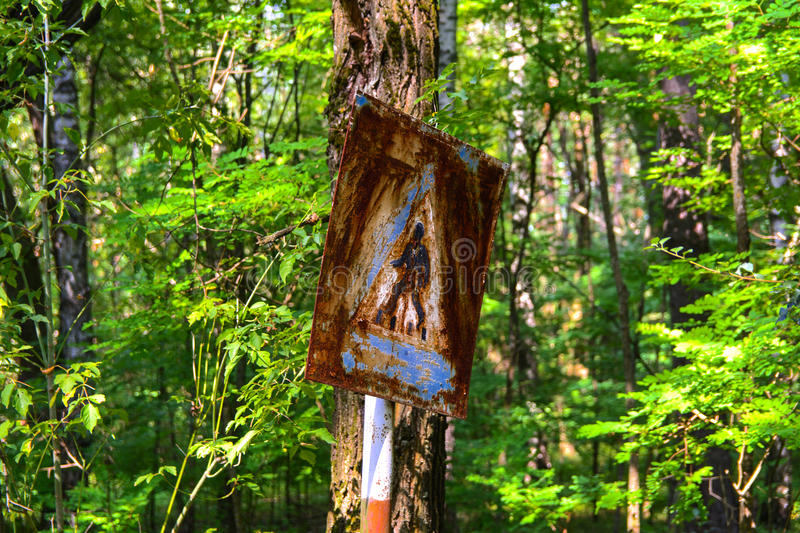 Old rusty signs of caution on the tree. Dead military unit. stock image