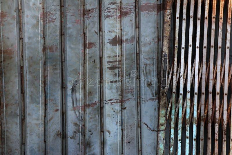 Old rusty sliding steel shutter door, grunge metal texture stock images