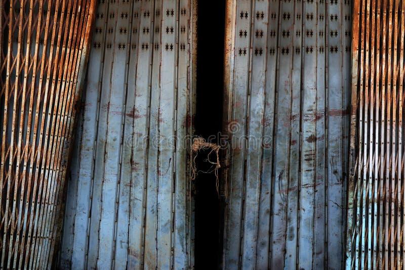 Old rusty sliding steel shutter door, grunge metal texture stock photos