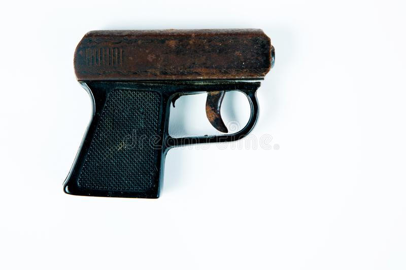 Old rusty starting pistol with black plastic grip. On white background, side view royalty free stock image