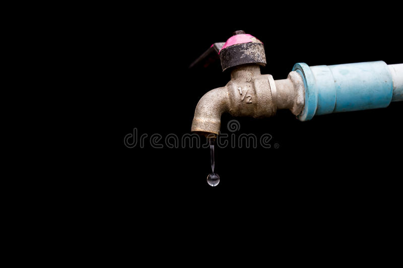 Old rusty tap leaking water. Old rusty tap leaking water isolate on black background stock image
