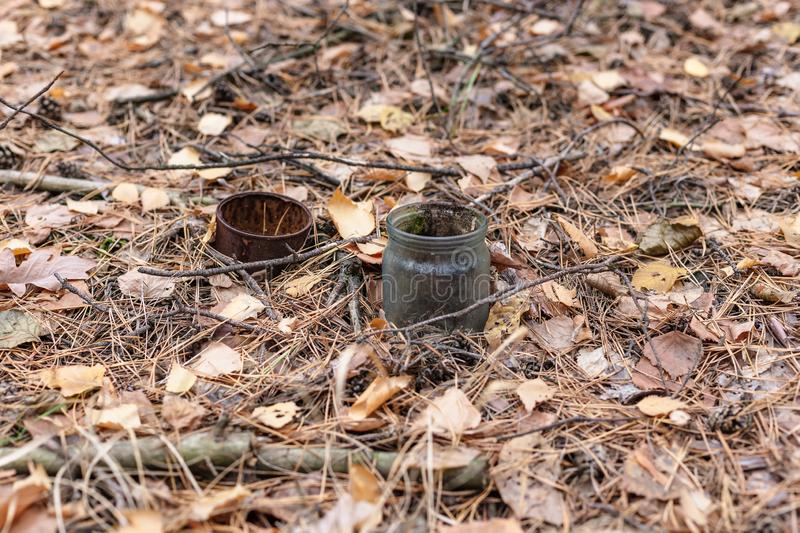 Old rusty tin can and glass jar on the ground in a pine forest. The concept of environmental pollution.  stock images