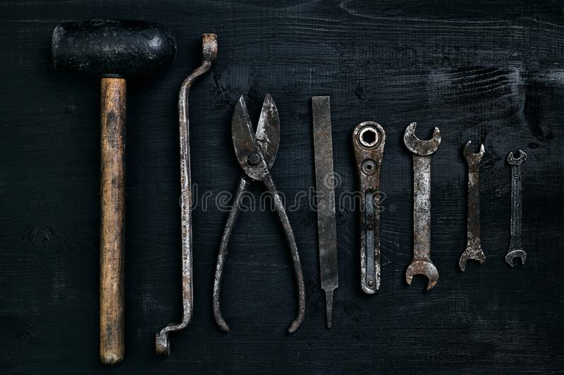 Old, rusty tools lying on a black wooden table. Hammer, chisel, metal scissors, wrench. royalty free stock photos