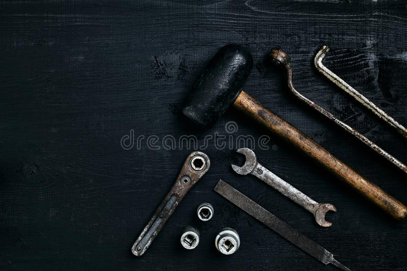 Old, rusty tools lying on a black wooden table. Hammer, chisel, metal scissors, wrench. stock photography
