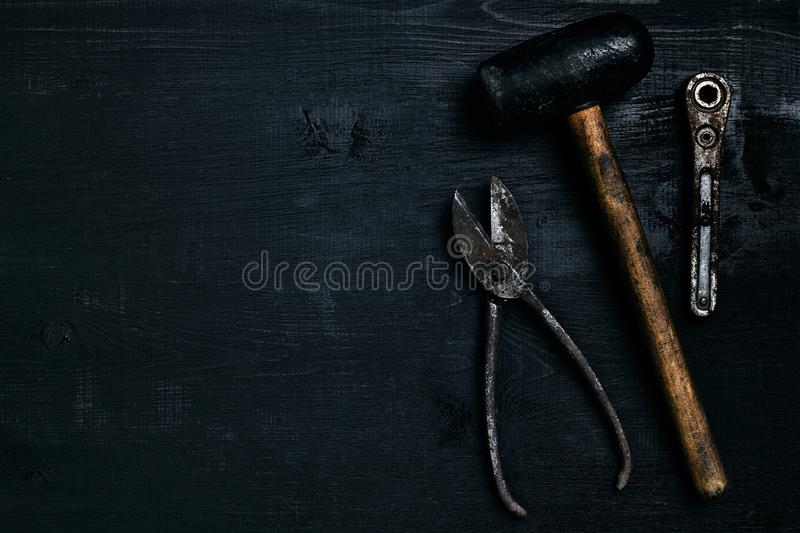 Old, rusty tools lying on a black wooden table. Hammer, chisel, metal scissors, wrench. Top view. Copy space. Still life. Flat lay stock photos