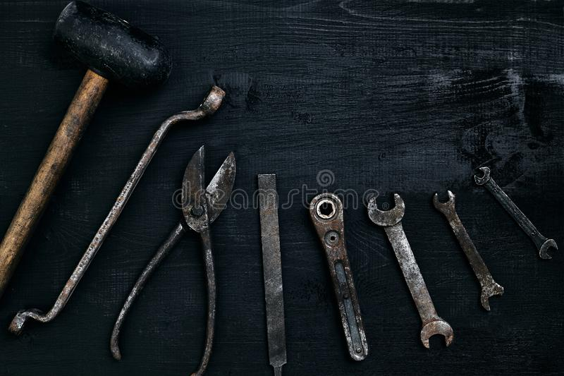 Old, rusty tools lying on a black wooden table. Hammer, chisel, metal scissors, wrench. royalty free stock image