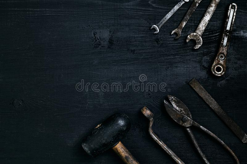 Old, rusty tools lying on a black wooden table. Hammer, chisel, metal scissors, wrench. stock photos