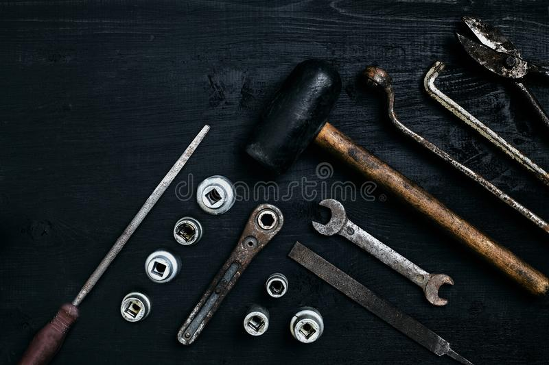 Old, rusty tools lying on a black wooden table. Hammer, chisel, metal scissors, wrench. stock image