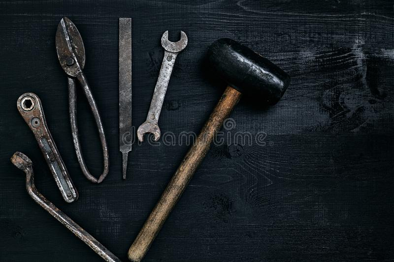 Old, rusty tools lying on a black wooden table. Hammer, chisel, metal scissors, wrench. royalty free stock photo
