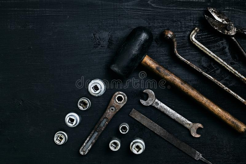 Old, rusty tools lying on a black wooden table. Hammer, chisel, metal scissors, wrench. royalty free stock photography