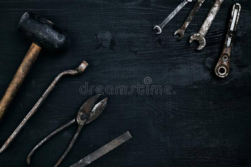 Old, rusty tools lying on a black wooden table. Hammer, chisel, metal scissors, wrench. royalty free stock images