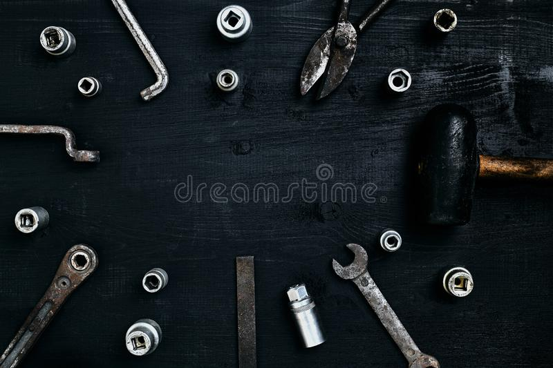 Old, rusty tools lying on a wooden table. Hammer, chisel, metal scissors, wrench, chisel. stock photo