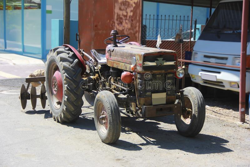 Old rusty tractor with four wheels on the street stock photography