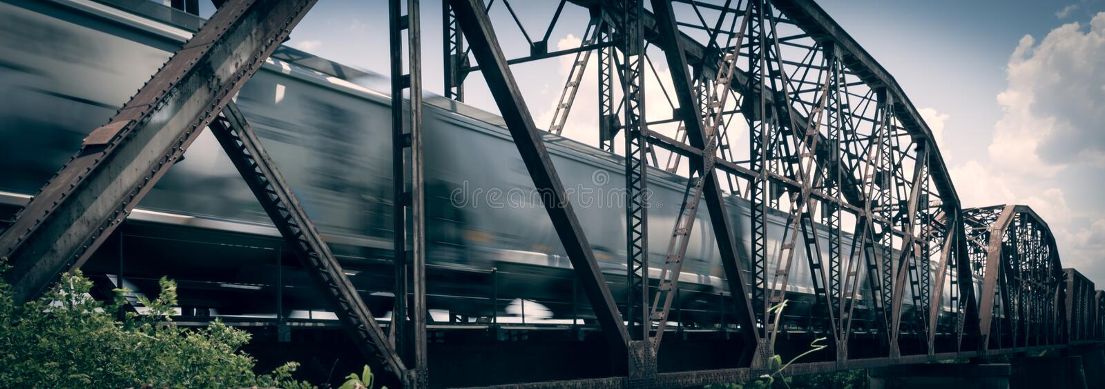 Old rusty truss bridge with moving freight train over the Red Ri royalty free stock photography