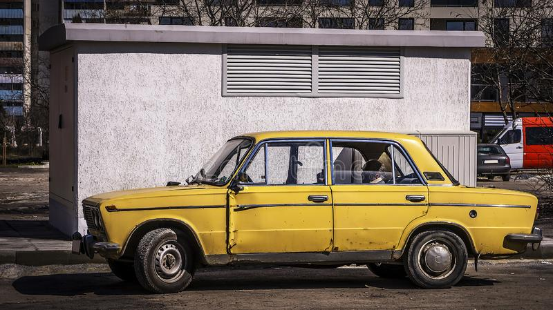 Old Russian car shot in street photography in Burgas / Bulgaria / 03.09.2018 /. Old rusty and unsupported yellow Russian car with a passenger in the rear seat stock photography
