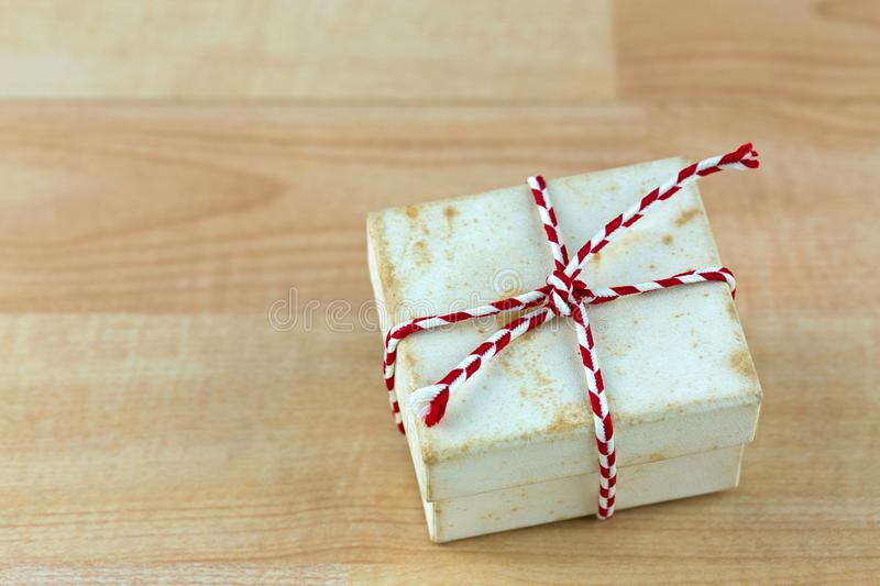 Old rusty vintage present gift box with stains tied with red white striped rope on wooden background royalty free stock photo