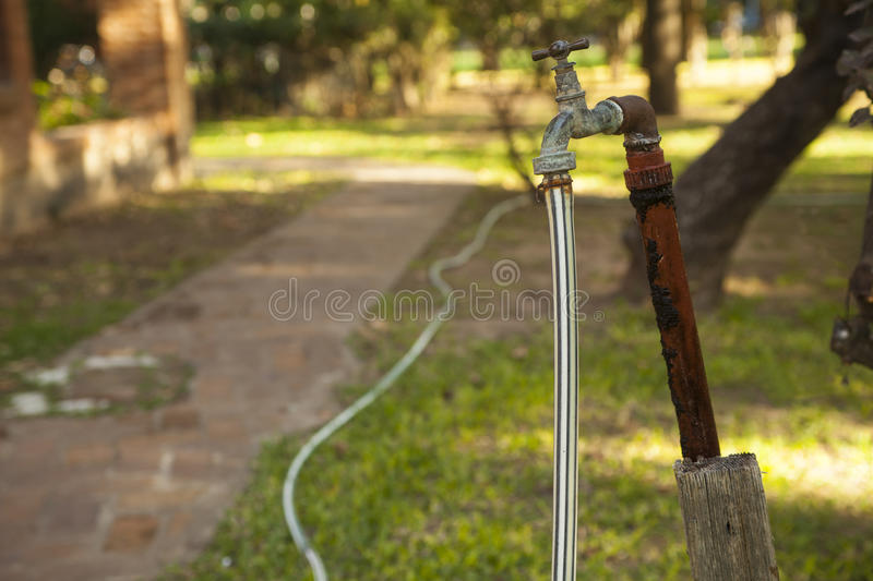 Old rusty water tap with hose in garden royalty free stock photography