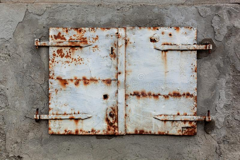 Old, rusty and weathered metal window coverings, closed shut stock photography