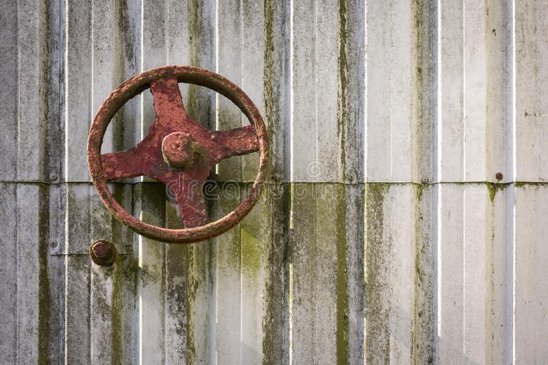 An old rusty wheel on a sheet metal wall royalty free stock photo