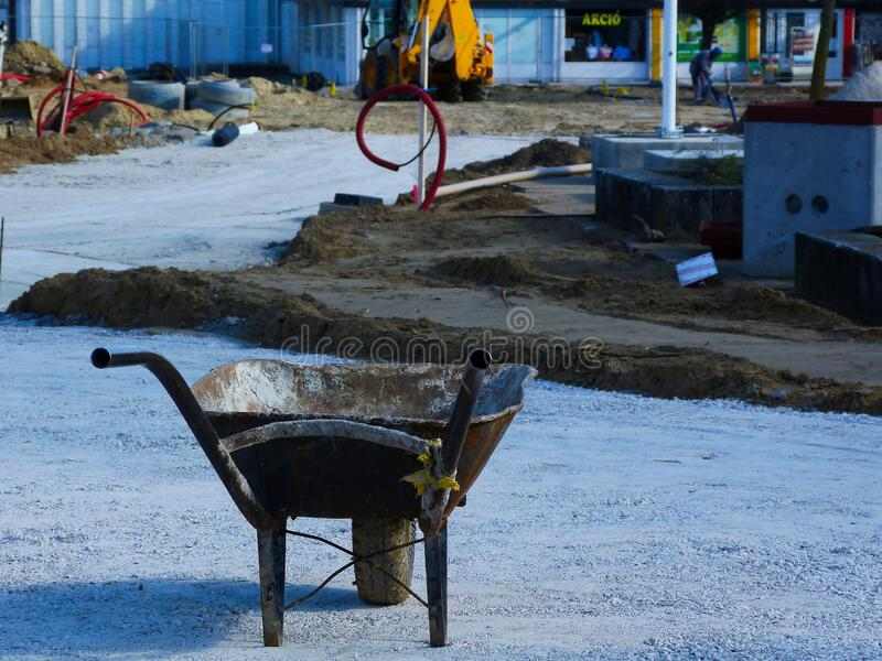 Old rusty wheelbarrow on construction site in diminishing perspective. And blurry background. selective focus. heavy earth moving equipment at far. old and new stock images