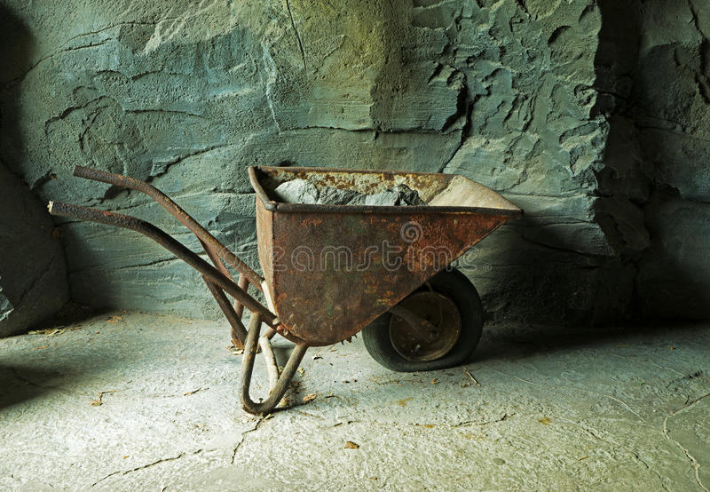 Old rusty wheelbarrow with ore at the mine at stone wall. Old rusty wheelbarrow with ore at the mine at the stone wall stock photography