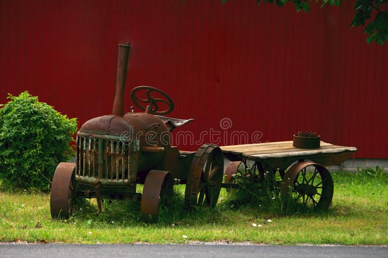 Old rusty wheeled tractor on the lawn. Old rusty wheeled tractor with a cart on the lawn by the fence royalty free stock photo