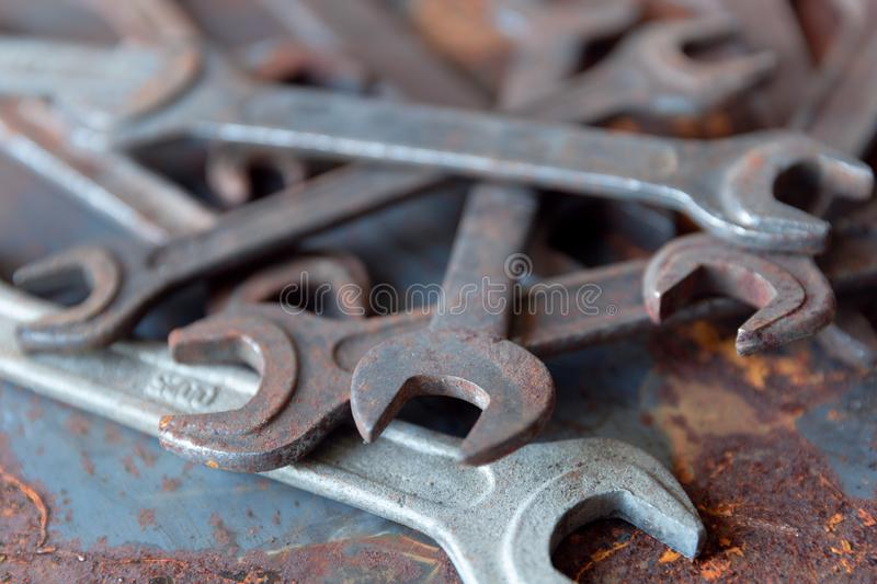 Old rusty wrench over battered metal table rough style. Wrenches top view for construction, industrial, electrician concept design. In natural light stock photography