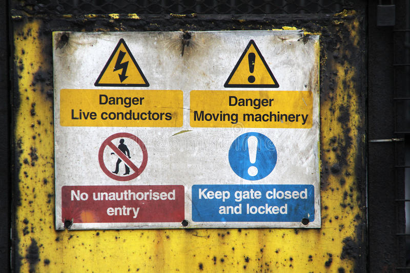Old safety warning signs. Old safety warning signs for electrical conductors and moving machinery stock photo