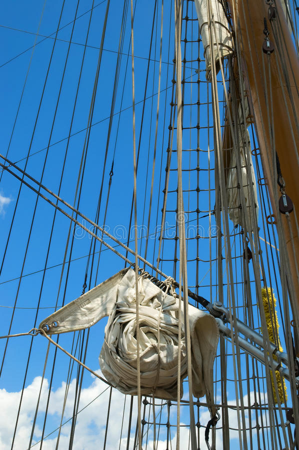 Old sailing ship. Sail and mast of old ship on a blue sky background royalty free stock image