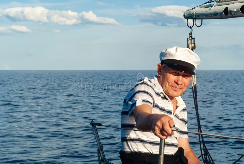 Old sailor in the seascape. Old sailor on his sailboat against a seascape stock photography