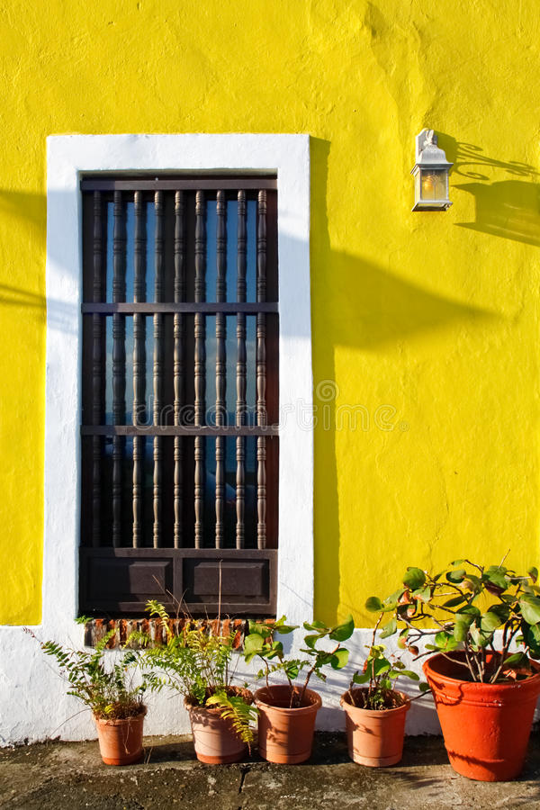 Old San Juan - Yellow Walls, Potted Plants. A shot of one of the vibrant colorful walls found throughout Old San Juan, Puerto Rico. This charming Caribbean city royalty free stock photo