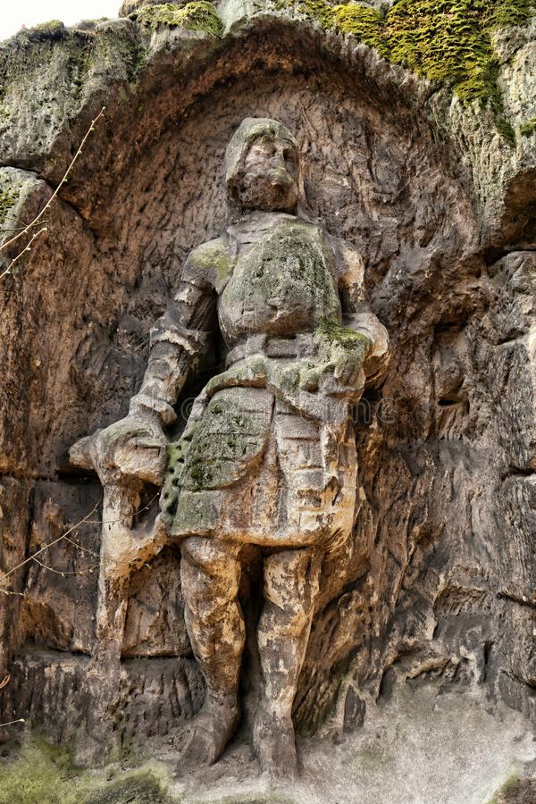 Old sand stone figure of the knight in rock recess stock image