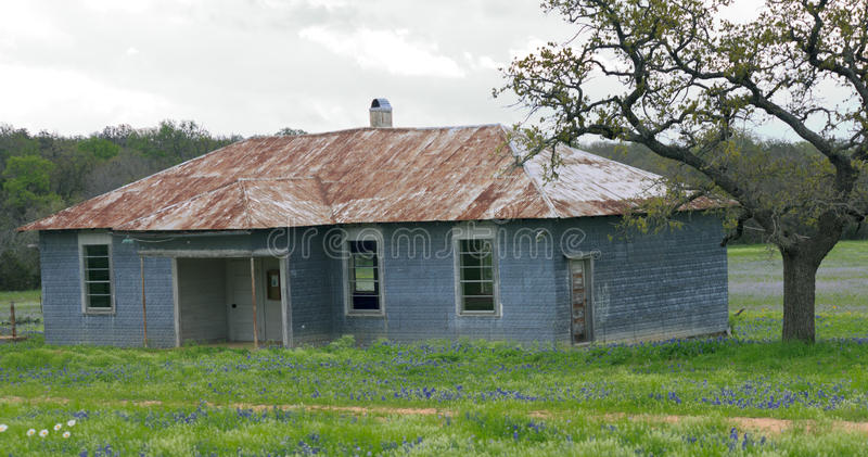 Old Sandy School House. In a rural setting with bluebonnets and hills. 1880's royalty free stock photos