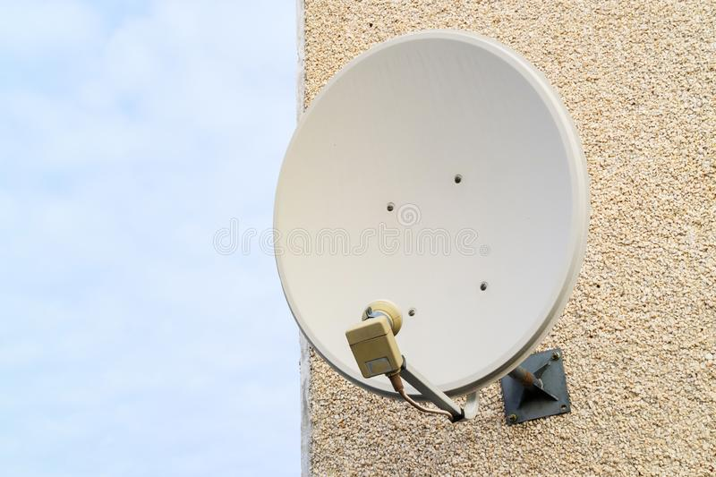 Old satellite dish mounted on the wall of the house, the wall of the house of small stone chips. Satellite TV royalty free stock photos
