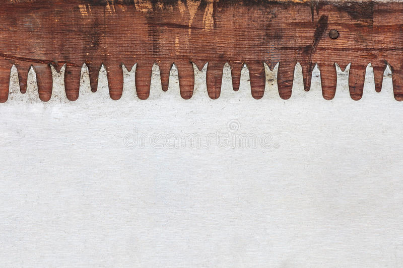 Old saw blade on weathered wood. Detail of a vintage saw blade on weathered wood royalty free stock image