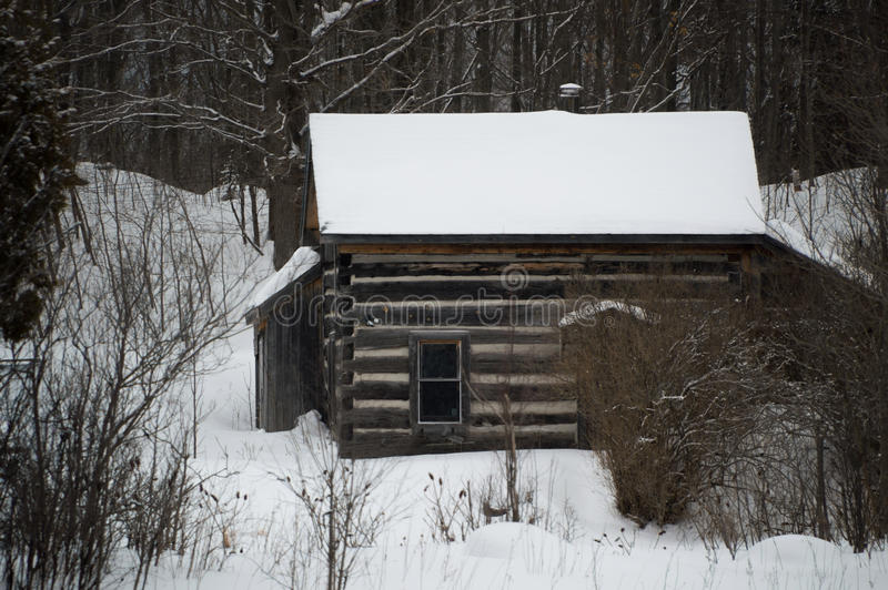Old sawn log cabin in the snow in winter landscape royalty free stock photography