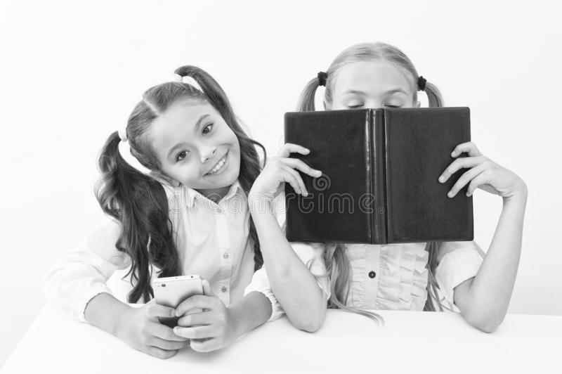 Old school against modern. Schoolgirl hold mobile phone modern smartphone while her friend enjoy old book as analog data royalty free stock photos