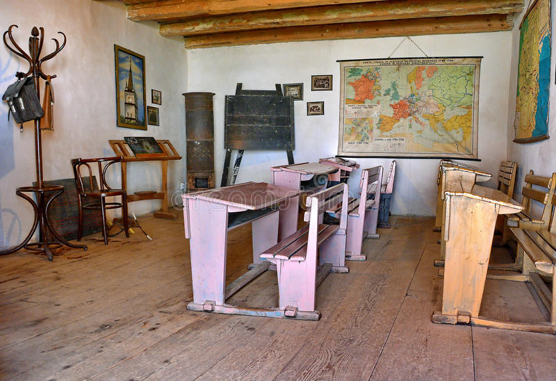 Old School Classroom. With wooden desks, maps and blackboard in Romania stock photos