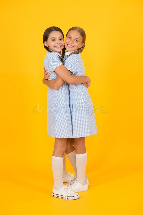 Old school. kid fashion. happy friends embrace on yellow background. fashion beauty. childhood happiness. sisterhood of. Small girls in retro school uniform royalty free stock images