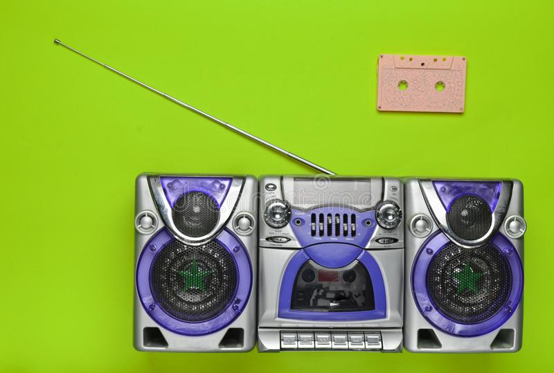 Old school retro tape recorder and audio cassette on a green background. Obsolete technologies. Trend of minimalism. Top view. stock photos