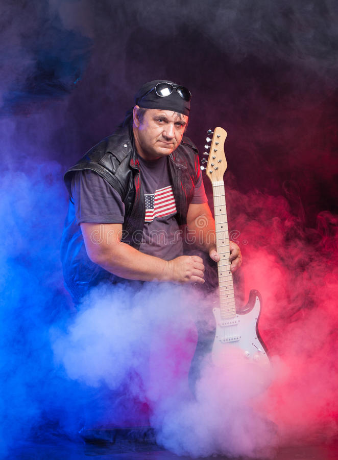 Old school rock musician is playing guitar. royalty free stock images