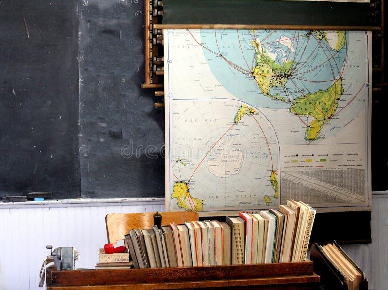 Old school room teacher`s desk, chalkboard and vintage map royalty free stock image