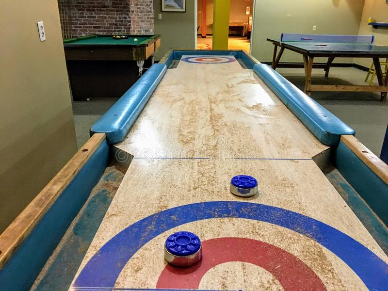 An old school shuffleboard table with blue shuffleboard pucks on top of it. The table is in a games room with a ping pong and pool. Table in the background royalty free stock photos